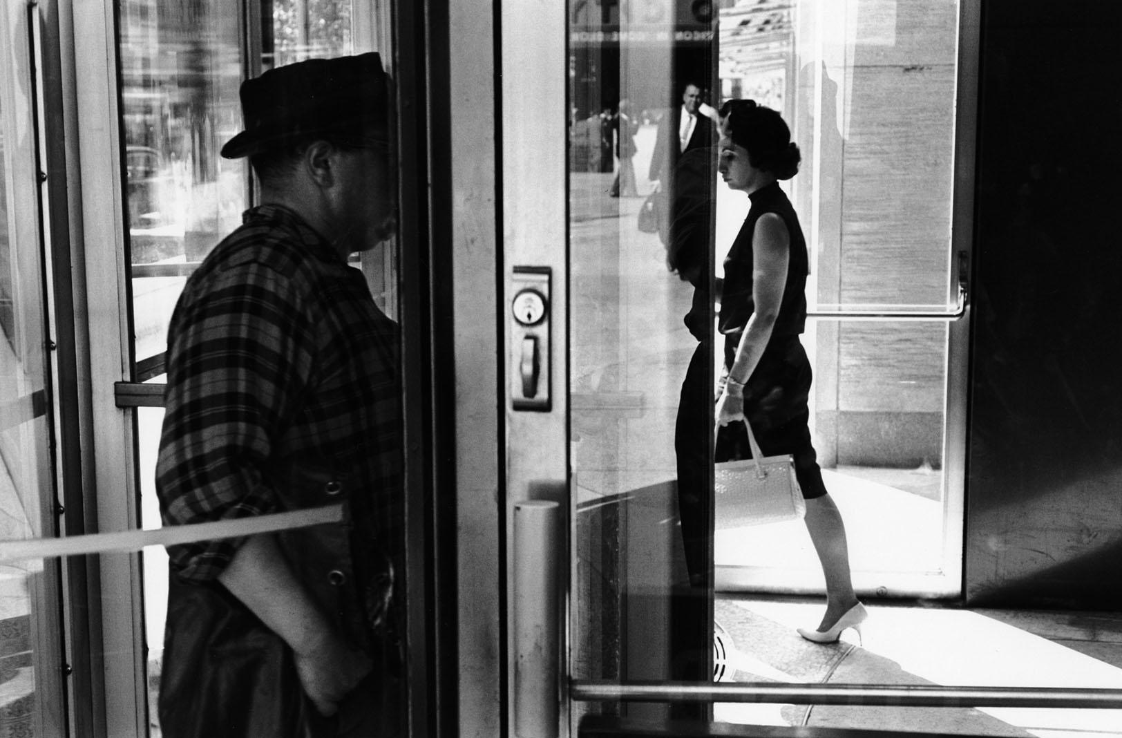 Imagen e un hombre y una mujer en una puerta giratoria