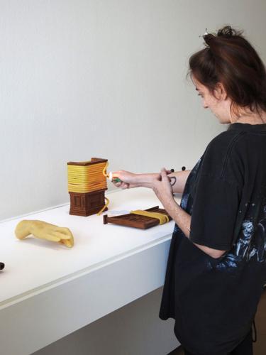 Una de las colaboradoras prendiendo una mecha durante la performance inaugurativa