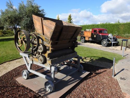 Estrujadora y Camioneta de transporte en el jardín del Museo del Vino Pagos del Rey